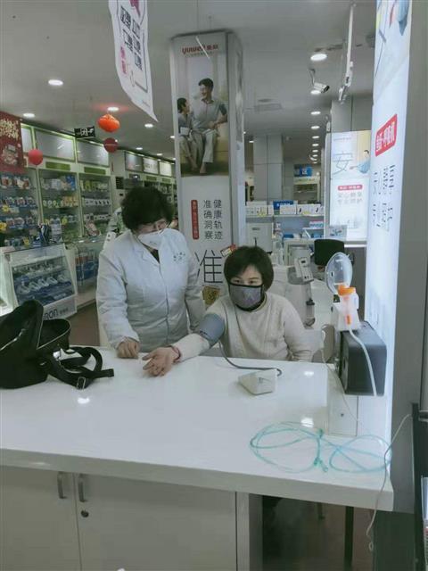 魏雪鸿为顾客测量血压。