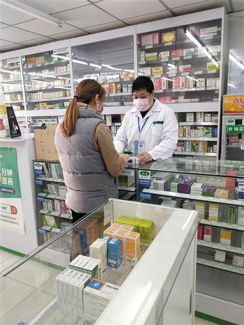 疫情防控时期,魏骏在药店为顾客提供药学服务。